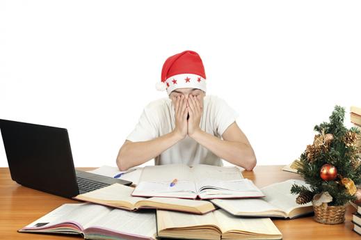 Sleepy student wearing santa hat while studying
