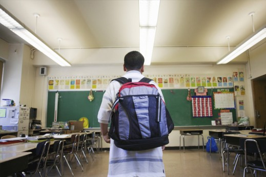 boy wearing backpack in school