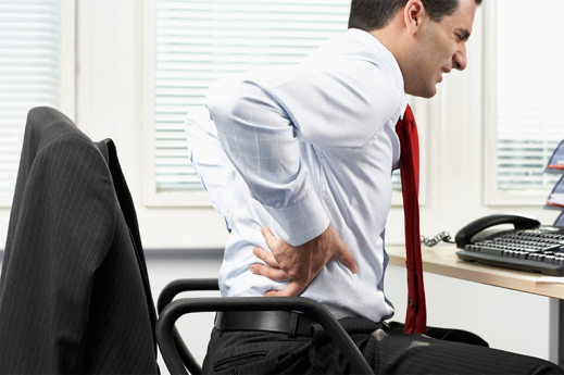 man sitting at desk with visible back pain