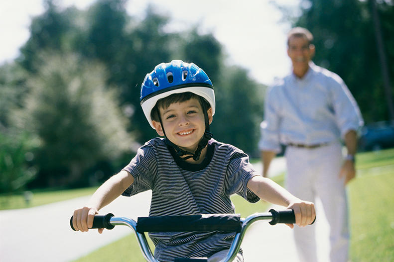 child riding bicycle with helmet