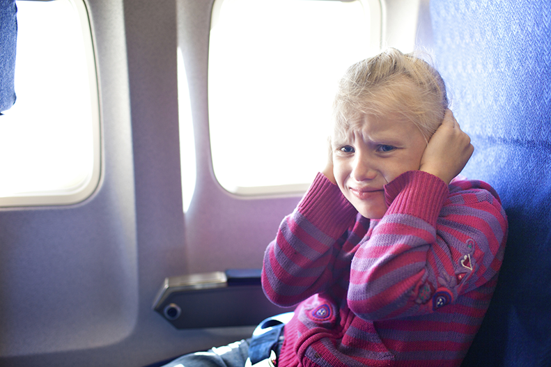 holding ears on airplane