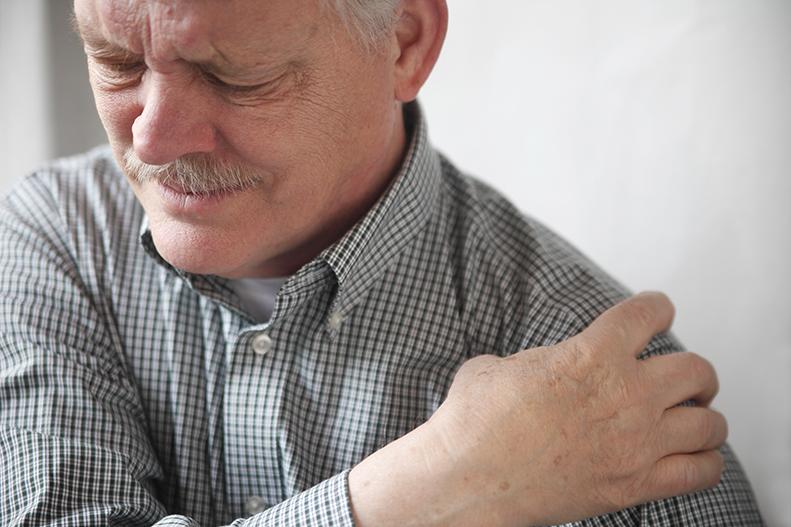 man clutching sore shoulder