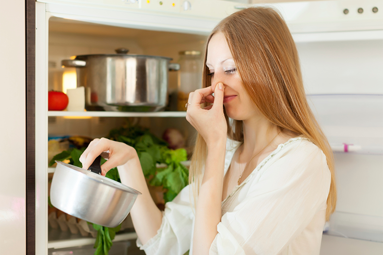 woman holding spoiled food in refrigerator