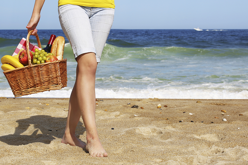 woman on beach with fruit