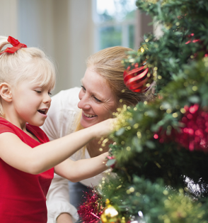 girl and mother by Christmas tree